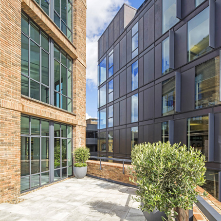 view between two buildings reflecting each other on a sunny day, with courtyard garden on one level