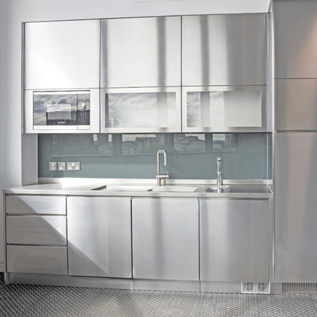 chrome effect kitchenette with sink, drawers, grey cupboards with transparent glass panels, reflecting the buildings outside