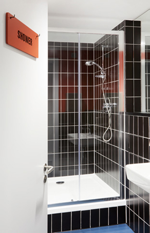 brown and burgundy tiled shower with glass doors and 'shower' plaque on the outside door
