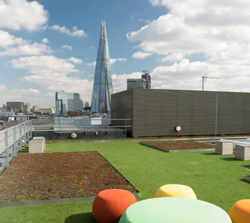 green and brown turfed rooftop terrace with seating and view of the Shard with a few clouds