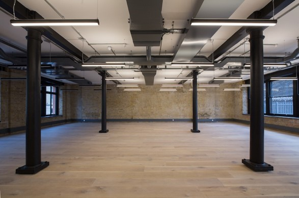 symmetrical workspace with black pillars wooden floors and brick walls in Southwark