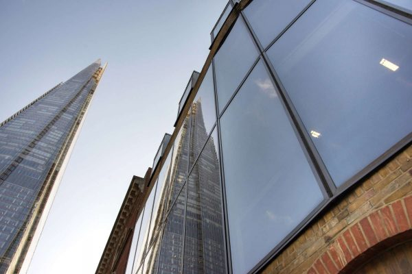a slim Shard stretches up into the blue sky and reflects in the windows on St Thomas Street