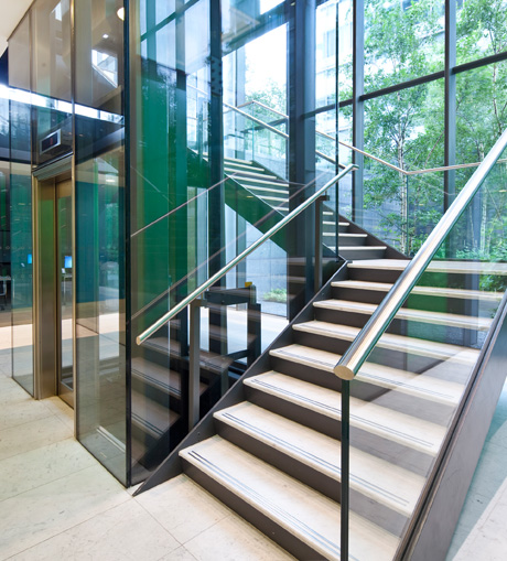 two short adjoining flights of stairs next to a lift going up, glass sides and polished rails