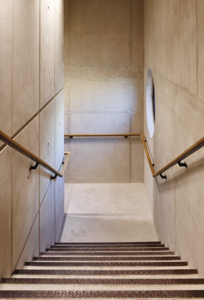 industrial effect staircase and railing with stone walls leading down