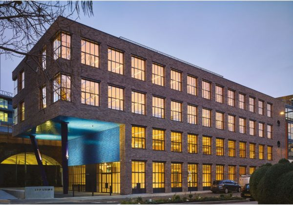 outside of building in the early evening shows warm golden light inside and blue light projected onto the outside