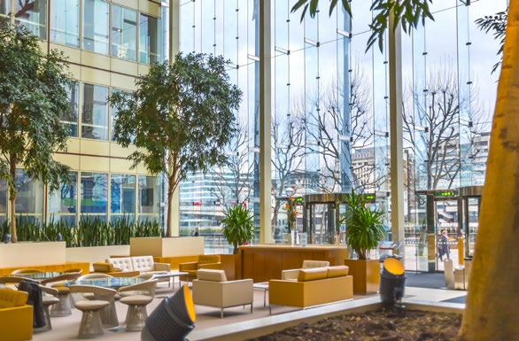 ground floor business lounge with mustard and brown furnishing, indoor plants and trees, high ceilings and view of buildings through the glass