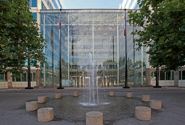 water fountain and flag poles in front of impressive floor-to ceiling glass exterior