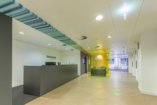 blue striped design above reception desk, wooden floors and waiting area behind a transparent yellow screen