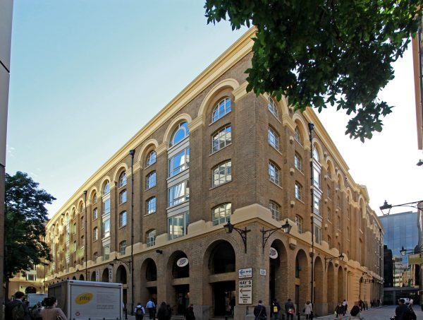 corner view of the sides of Shackleton House on a busy street, Boots and HAY'S GALLERIA sign posted in the arches