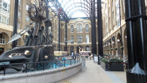 massive iron sculpture depicting battle water vessel, enclosed with barricades between buildings