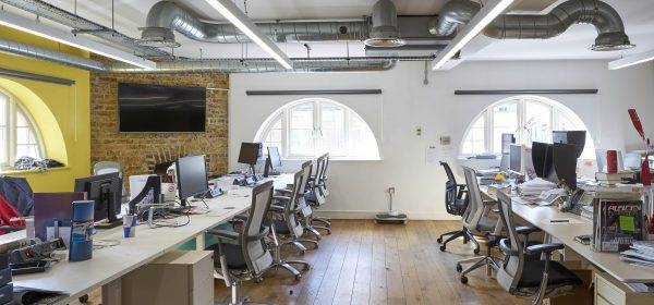 long desks of work stations in use, wooden floors and crescent shaped downs with a screen mounted on a side brick wall