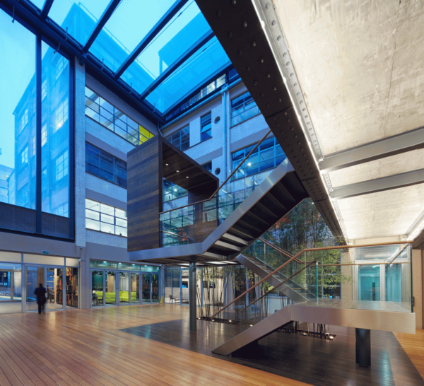 huge glass sides and ceiling reflecting a blue light, a staircase in the foyer climbing up three flights