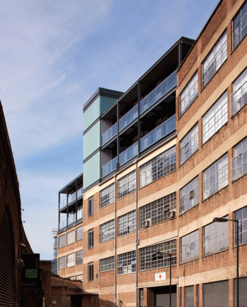 a glass top peaks out above rows of windows and brick levels below in Southwark