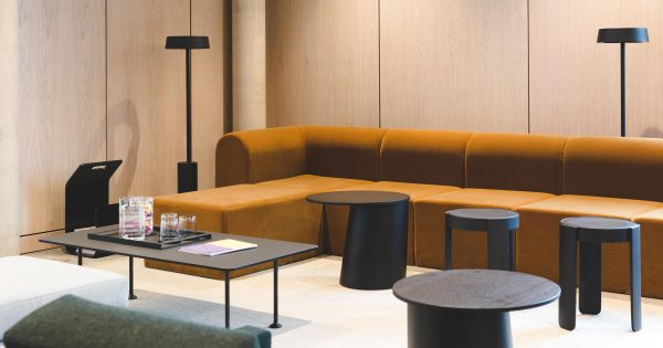 long mustard swede velvet sofa with wooden wall panneling, stools and coffee tables with jugs of water refreshment