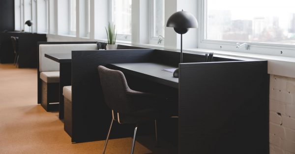 dark brown and grey booths and work areas are decorated with small plants and lamps, alongside the windows