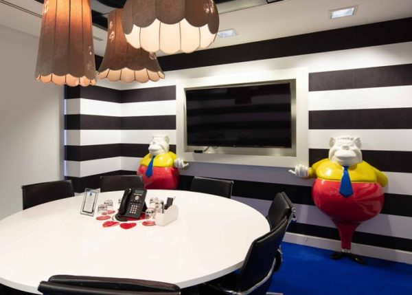 """alt=""""tweedle dum and tweedle dee holding screen in a meeting room with black and white striped wall, round table and chairs and phone"""""""