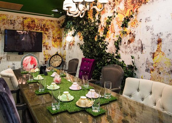 Mad Hatter style meeting room with wall creeper, vibrant coloured walls and furniture with tea cups set on green turf table piece
