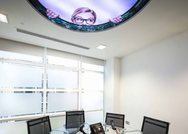 Alice in Wonderland inspired ceiling with woman's face peering in and meeting room below