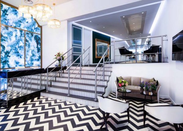 break out area with black and white zigzag tiled floor, flowers on tables and blue and white tie dye design on one wall and stairs leading up to higher level tables and chairs