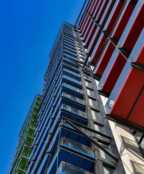 angled view looking up at modern building front on the Albert Embankment with green, blue and red balcony bottoms, and a blue sky