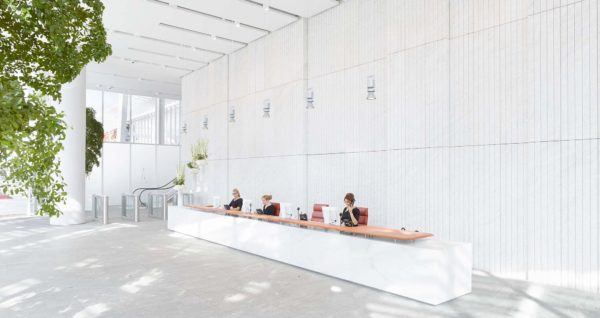 huge bright white lobby reception, indoor trees and flowers, barriers and escalator leading upwards