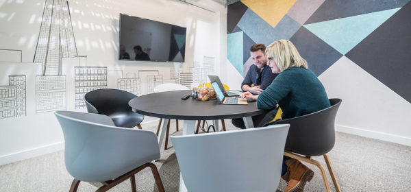 meeting room with blue and grey furniture and shapes on one wall with sketch of London skyline on the other