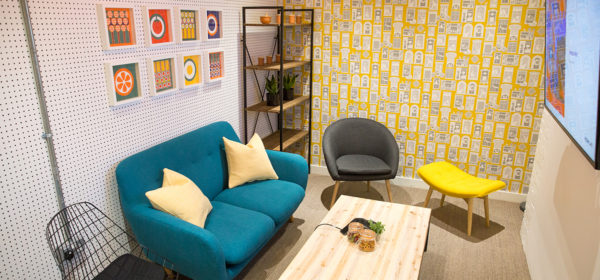 retro meeting room with colourful patterned wallpaper and funky furniture, jars of sweets and pretzels on the table and plants on shelves